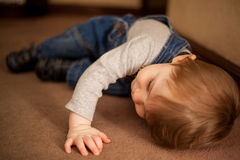 Netter Junge, der auf den Teppich legt Lizenzfreies Stockbild