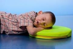 Netter Junge, der auf einem Kissen schläft Stockbilder