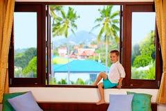Netter Junge, der auf Fensterbrett in den Tropen sitzt lizenzfreie stockfotografie