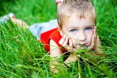 Netter Junge, der auf grünem frischem Gras sich entspannt Stockbild