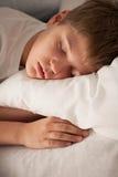 Netter Junge, der auf Kissen schläft Lizenzfreie Stockfotos