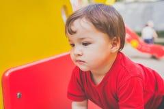 Netter Junge, der auf Spielplatz spielt lizenzfreie stockbilder
