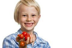Netter Junge, der Bündel Tomaten hält Stockbilder