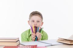 Netter Junge, der bei Tisch sitzt und bunte Bleistifte hält Stockfotografie