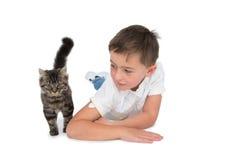 Netter Junge, der das graue Kätzchen liegt auf Boden betrachtet Stockfotos