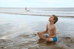 Netter Junge, der in der Lotosyogahaltung auf Strand sich entspannt Lizenzfreies Stockbild