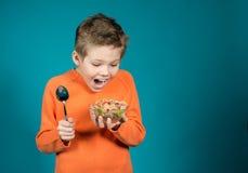 Netter Junge, der die Getreide lokalisiert auf blauem Hintergrund isst Stockfoto
