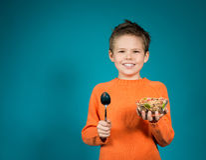 Netter Junge, der die Getreide lokalisiert auf blauem Hintergrund isst Stockfotos