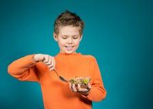 Netter Junge, der die Getreide lokalisiert auf blauem Hintergrund isst Lizenzfreie Stockfotos