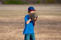 Netter Junge, der draußen Baseball spielt Stockbilder