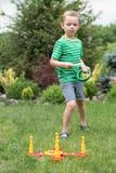Netter Junge, der drau?en werfende Ringe eines Spiels in Sommer Park spielt Die Freude am Sieg stockbild