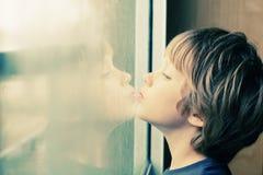 Netter Junge, der durch das Fenster schaut Lizenzfreies Stockfoto