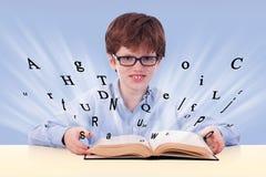 Netter Junge, der ein Buch auf seinem Schreibtisch liest lizenzfreie stockbilder