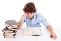 Netter Junge, der ein Buch auf seinem Schreibtisch studiert und liest Stockbild