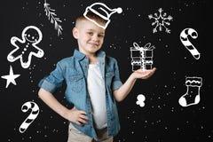 Netter Junge, der ein Geschenk beim Feiern des neuen Jahres hält Lizenzfreies Stockbild
