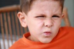 Netter Junge, der ein unverschämtes Grinsen bildet Stockfotografie