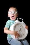 Netter Junge, der eine Borduhr anhält Lizenzfreies Stockfoto