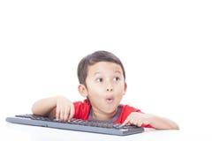 Netter Junge, der eine Tastatur verwendet Stockbilder