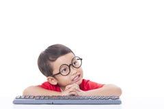 Netter Junge, der eine Tastatur verwendet Lizenzfreie Stockbilder