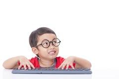 Netter Junge, der eine Tastatur verwendet Stockbild