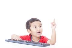 Netter Junge, der eine Tastatur verwendet Stockfoto