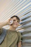 Netter Junge, der einen Handy verwendet lizenzfreies stockfoto