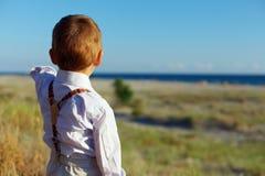 Netter Junge, der etwas auf dem Abstand zeigt Stockfotos