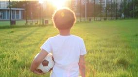 Netter Junge, der Fußball mit Fußballball auf dem Sonnenuntergang im Park spielt S stock video
