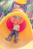 Netter Junge, der im Tunnel auf Spielplatz spielt Stockfotos