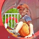 Netter Junge, der im Tunnel auf Spielplatz spielt Lizenzfreie Stockfotografie