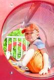 Netter Junge, der im Tunnel auf Spielplatz spielt Stockfoto