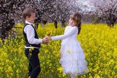 Netter Junge, der Mädchenblumen gibt Stockbild