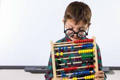 Netter Junge, der mit Abakus im Klassenzimmer spielt Stockfotografie