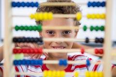 Netter Junge, der mit Abakus im Klassenzimmer spielt Stockfotos