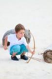 Netter Junge, der mit Bogen und Pfeilen spielt Stockbilder