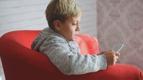 Netter Junge, der mit einem Smartphone spielt stock video