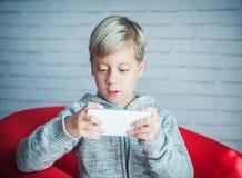 Netter Junge, der mit einem Smartphone spielt Lizenzfreies Stockfoto