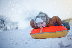 Netter Junge, der mit Schläuche im Schnee, Winterzeit, Glückkonzept schiebt Lizenzfreies Stockfoto