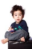 Netter Junge, der mit tragbarem Gerät sitzt Stockfotos