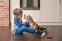 Netter Junge, der mit Welpenenglischbulldogge spielt stockfotografie