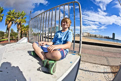 Netter Junge, der am Rochenpark sitzt Stockfotografie