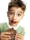 Netter Junge, der Schokolade isst Stockfotos