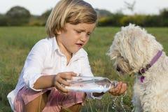 Netter Junge, der seinem Hund Wasser gibt Stockfotografie