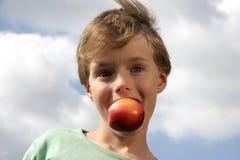 Netter Junge, der Spaß mit einem Pfirsich bildet Lizenzfreies Stockfoto