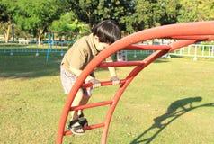 Netter Junge, der am Spielplatz spielt Stockfotos