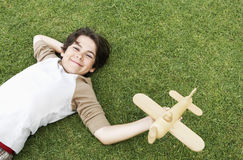 Netter Junge, der Toy Airplane While Lying On-Gras hält Lizenzfreies Stockfoto