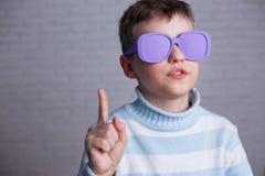 Netter Junge in der violetten Sonnenbrille mit undurchsichtigen Linsen aufwärts zeigend lizenzfreies stockfoto