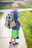 Netter Junge, der weg morgens zur Schule vorangeht Stockbilder