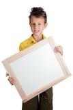 Netter Junge, der weißes Brett hält Stockfotografie