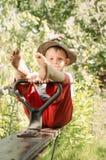 Netter Junge des kleinen Landes, der in einem Garten sitzt Lizenzfreie Stockfotos
